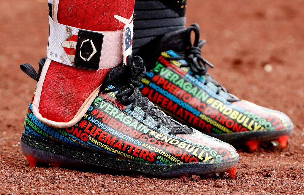 . Cleveland Indians\' Francisco Lindor wears cleats featuring popular hashtags during the first inning of a baseball game against the Kansas City Royals Sunday, Aug. 26, 2018, in Kansas City, Mo. (AP Photo/Charlie Riedel)