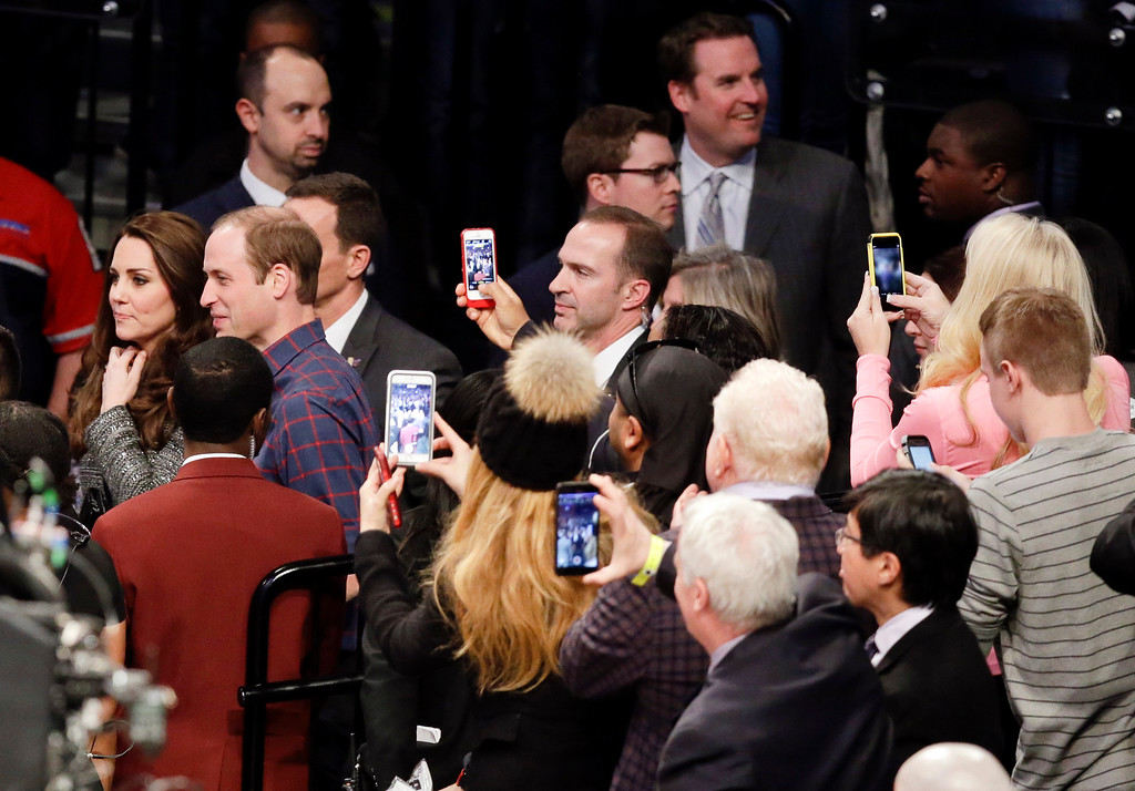 . Onlookers take photographs of Britain\'s Prince William, right, and Kate, Duchess of Cambridge, as they arrive during the second half of an NBA basketball game between the Brooklyn Nets and the Cleveland Cavaliers, Monday, Dec. 8, 2014, in New York. (AP Photo/Frank Franklin II)