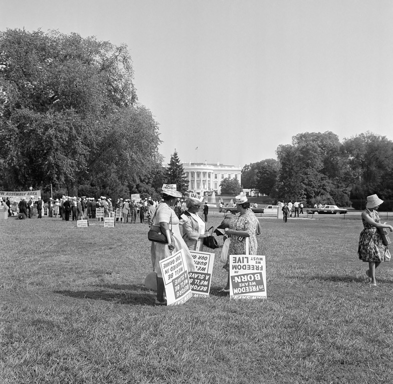 . Members of the United Automobile Workers delegation pick up signs on the Ellipse for March on Washington demonstration on August 28, 1963. In background is White House. (AP Photo)