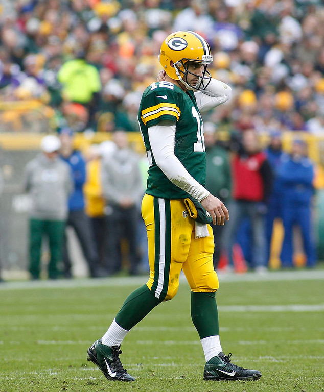 . Green Bay Packers quarterback Aaron Rodgers walks after being hit by the Minnesota Vikings during the first half of a NFL football game in Green Bay, Wisconsin December 2, 2012. REUTERS/Darren Hauck