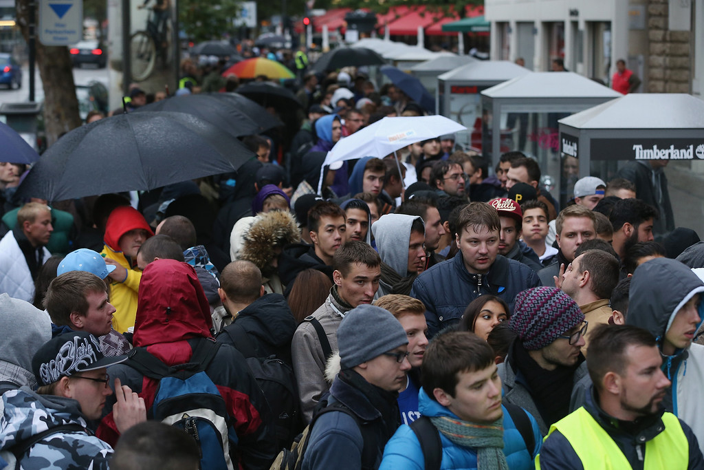 . People line up outside the Berlin Apple Store to buy the new Apple iPhone 5S and 5C smartphones on the first day of sales on September 20, 2013 in Berlin, Germany. The new iPhone 5S and 5C phones went on sale all over the world today and hundreds of customers waited outside the Berlin store in the rain to be among the first to buy the new phones starting at 8am.  (Photo by Sean Gallup/Getty Images)