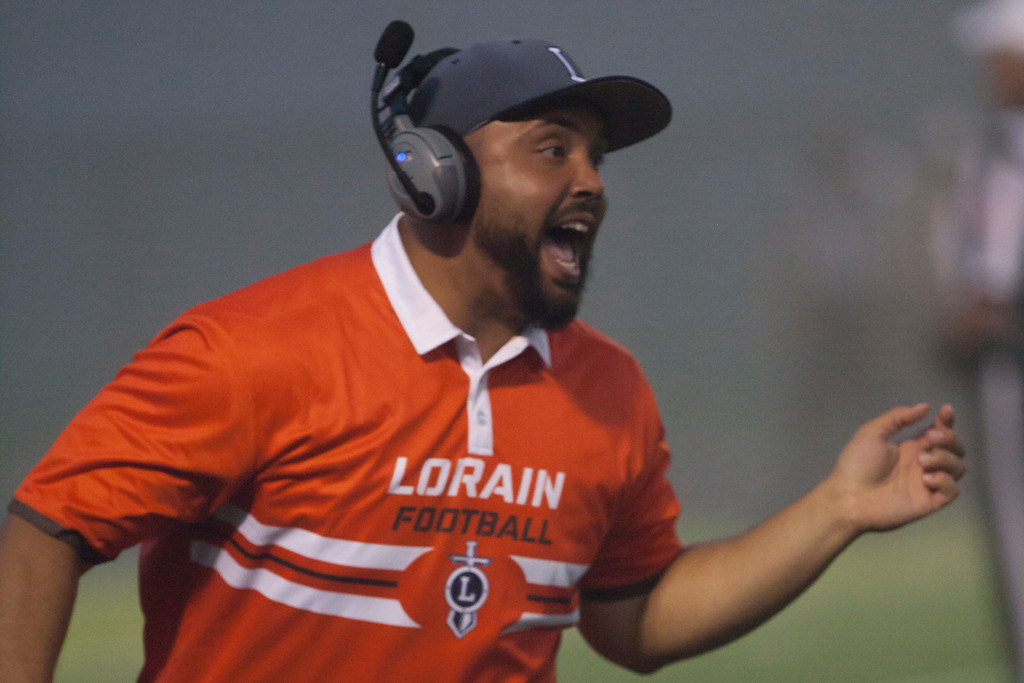 . Jen Forbus - The Morning Journal<br> Lorain coach Brian Joyner celebrates a Titans\' touchdown against St. Joseph on Sept. 14.
