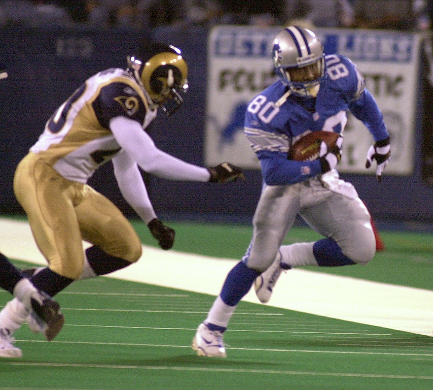 . Detroit Lions wide receiver Desmond Howard (right, #80) runs for yardage after a catch as St. Louis Rams safety Kim Herring (#20) prepares to tackle him during first quarter action in a game played at the Pontiac Silverdome in Pontiac, Mich., Monday, October 8, 2001.