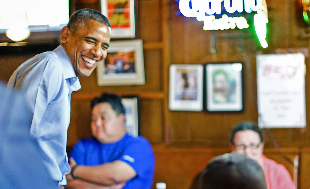 . President Barack Obama laughs with patrons at Matt\'s Bar, where he poked his head in while on the way to a town hall meeting at Minnehaha Falls in Minneapolis on Thursday. (Pioneer Press: Ben Garvin)