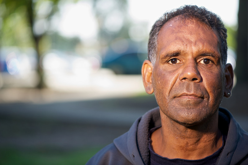 Mid-adult Aboriginal man looking at camera, photographed horizontally on a blurred background