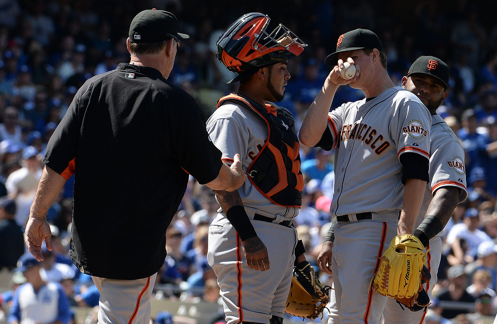 . San Francisco Giants starting pitcher Matt Cain, center, wipes his face as manager Bruce Bochy, left, prepares to take him out of the game in the sixth inning of a Major league baseball game against the Los Angeles Dodgers on Saturday, May 10, 2013 in Los Angeles.   (Keith Birmingham/Pasadena Star-News)