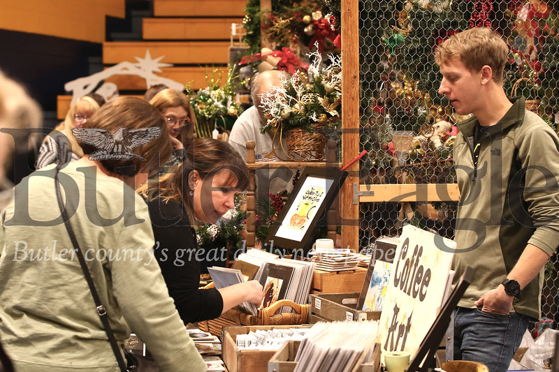 Craig Peterson of Art Work on the Run assists holiday shoppers at the Mars Area Fall Craft Show Saturday. Area residents and artisans packed Mars High School for the annual event that featured regional artists and craft makers. Seb Foltz/Butler Eagl