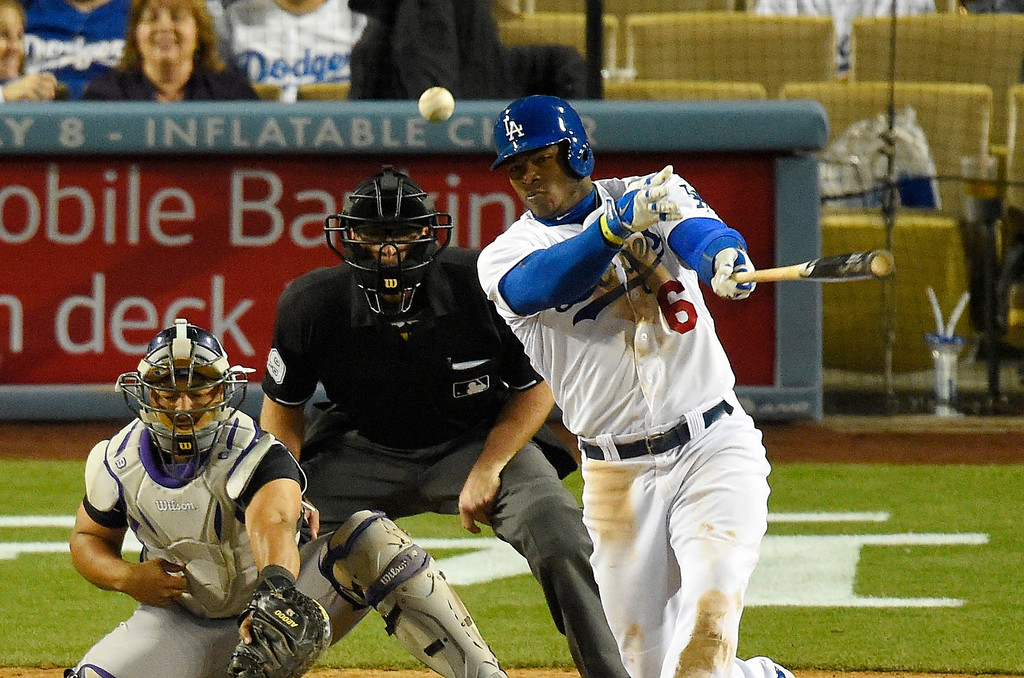. Los Angeles Dodgers\' Yasiel Puig, right, hits a ground-rule double as Colorado Rockies catcher Wilin Rosario, left, catches and home plate umpire Paul Nauert look on during the eighth inning of a baseball game, Saturday, April 26, 2014, in Los Angeles. (AP Photo/Mark J. Terrill)