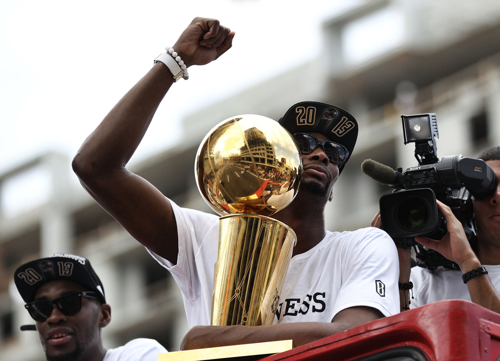 . Forward Chris Bosh #1 of the Miami Heat holds the Larry O\'Brien NBA Championship Trophy as he rides a bus during the championship victory parade on June 24, 2013 in Miami, Florida. The Miami Heat defeated the San Antonio Spurs in the NBA Finals. (Photo by Marc Serota/Getty Images)