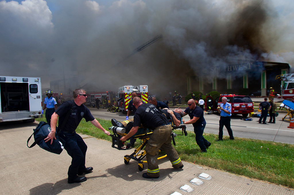 . A firefighter is wheeled to an ambulance after fighting a fire at the Southwest Inn, Friday, May 31, 2013, in Houston. A fire that engulfed a Houston motel has injured at least six firefighters, including two critically, and three people are missing. (AP Photo/Houston Chronicle, Cody Duty)