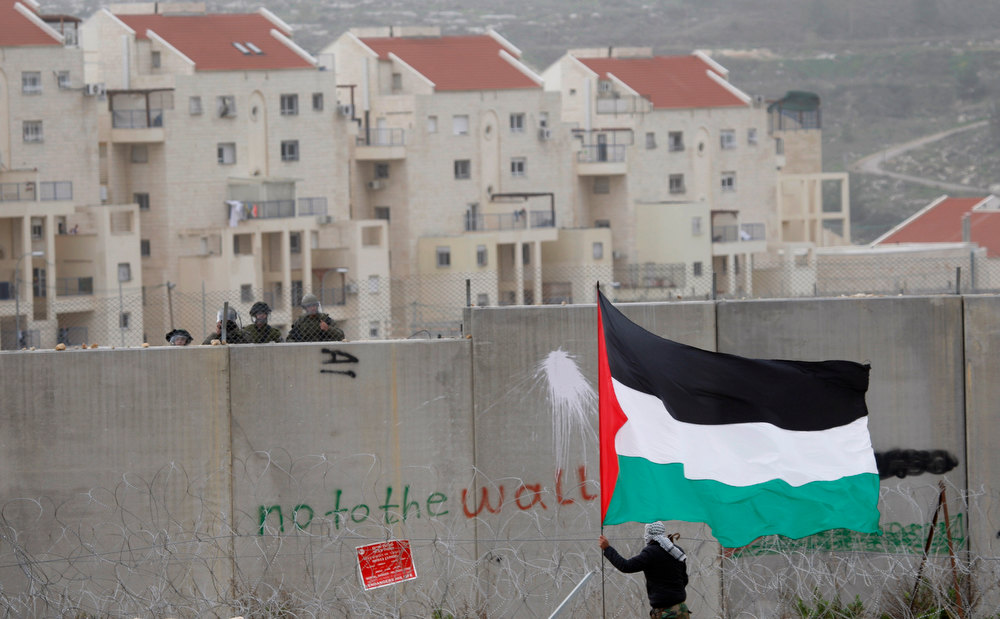". In this  Friday, Feb. 17, 2012 file photo, the West Bank Jewish settlement of Modiin Illit is seen in the background while a protestor waves a Palestinian flag in front of Israeli troops during a protest against Israel\'s separation barrier in the West Bank village of Bilin. The United Nations\' first report on the broad policy of Israeli settlements concluded Thursday that the government\'s practice of ""creeping annexation\"" clearly violates the human rights of Palestinians, and called for an immediate halt. (AP Photo/Majdi Mohammed, File)"