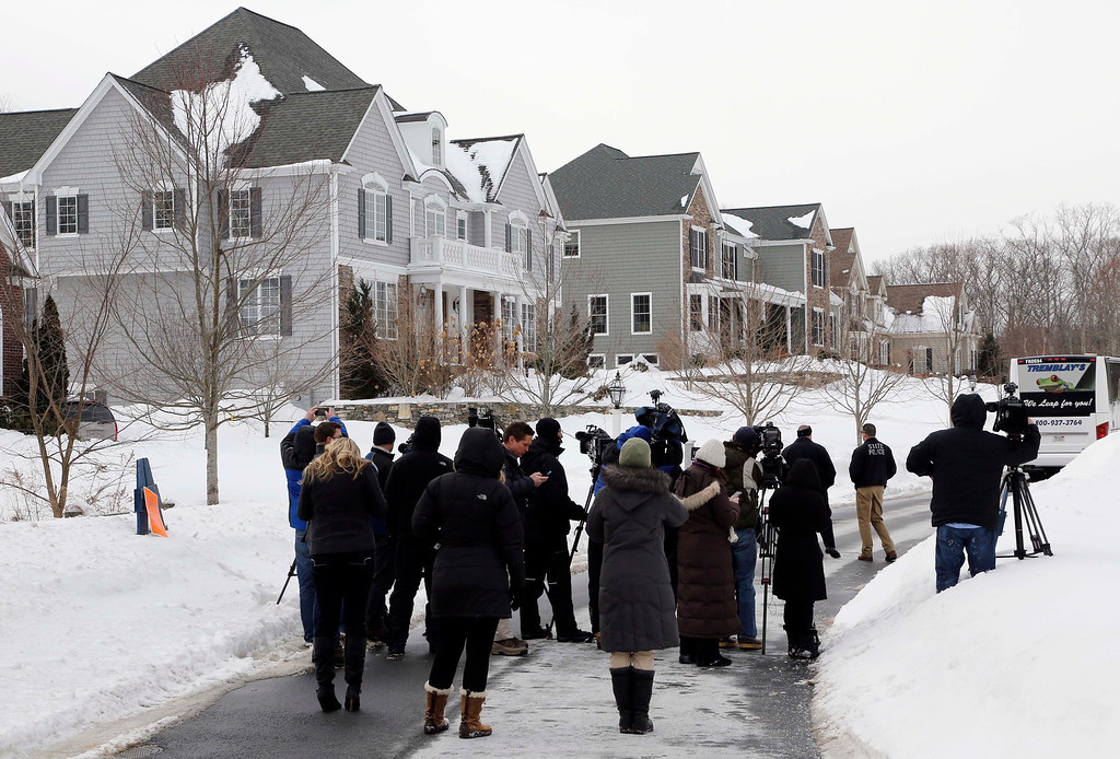 . Media members and police officers stand near a bus sitting in front of the North Attleborough, Mass., home of former New England Patriots football player Aaron Hernandez, rear, during a site visit by the jury in his murder trial Friday, Feb. 6, 2015. Hernandez is charged with killing semiprofessional football player Odin Lloyd in 2013. The jury was bused to several sites related to the case, including Hernandez\'s home, Lloyd\'s home, and the industrial park where Lloyd\'s body was found. (AP Photo/Steven Senne, Pool)