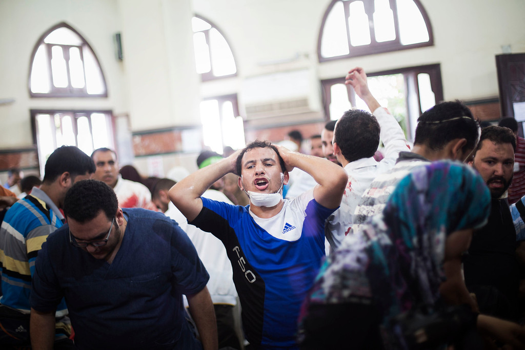 . An Egyptian man reacts while doctors treat a supporter of Egypt\'s ousted President Mohammed Morsi injured during clashes with security forces at Nasr City, where pro-Morsi protesters have held a weeks-long sit-in, in a field hospital in Cairo, Egypt, Saturday, July 27, 2013. Overnight clashes between security forces and supporters of ousted Egyptian President Mohammed Morsi in east Cairo left dozens of protesters dead following a day of massive pro-military rallies backing a tough hand against Morsiís backers and the Muslim Brotherhood group from which he hails.  (AP Photo/Manu Brabo)