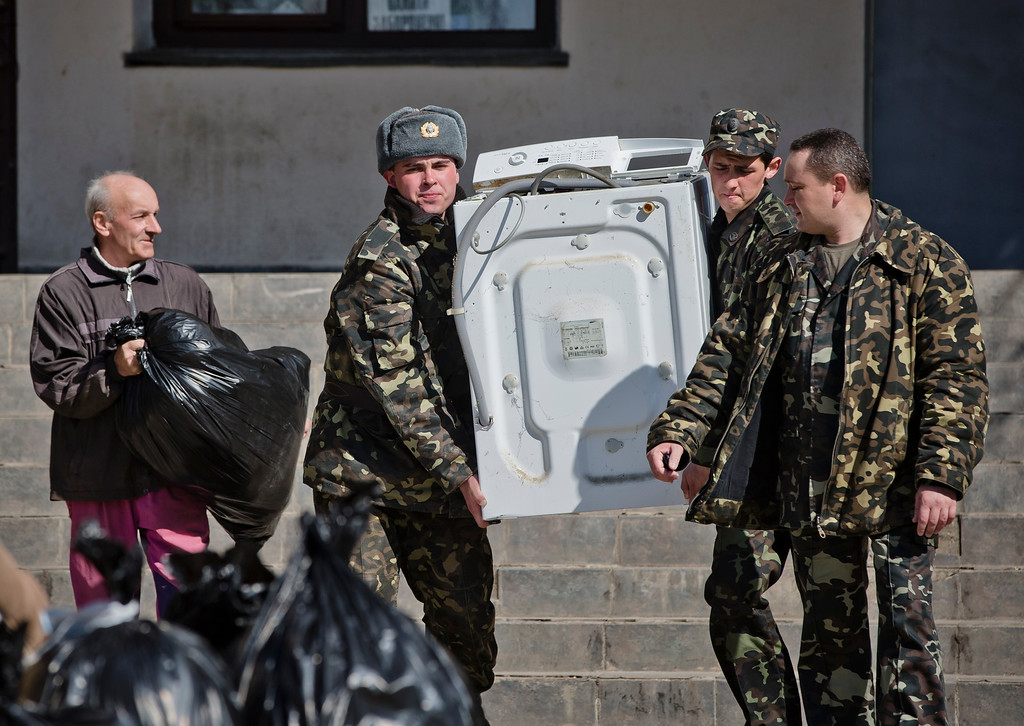 . Ukrainian airmen carry a washing machine while removing their belongings from the Belbek air base, outside Sevastopol, Crimea, Friday, March 21, 2014. The base commander Col. Yuliy Mamchur said he was asked by the Russian military to turn over the base but is unwilling to do so until he receives orders from the Ukrainian defense ministry. (AP Photo/Vadim Ghirda)