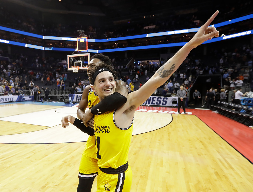 . UMBC\'s K.J. Maura (11) and Jourdan Grant celebrate the team\'s 74-54 win over Virginia in a first-round game in the NCAA men\'s college basketball tournament in Charlotte, N.C., Friday, March 16, 2018. (AP Photo/Gerry Broome)