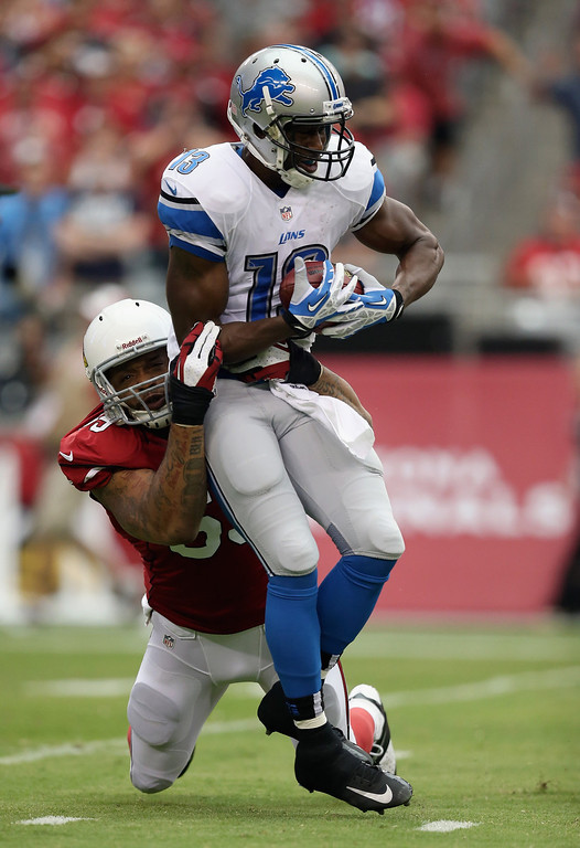 . Wide receiver Nate Burleson #13 of the Detroit Lions is hit for a loss by defensive end John Abraham #55 of the Arizona Cardinals in the first quarter at University of Phoenix Stadium on September 15, 2013 in Glendale, Arizona.  (Photo by Jeff Gross/Getty Images)