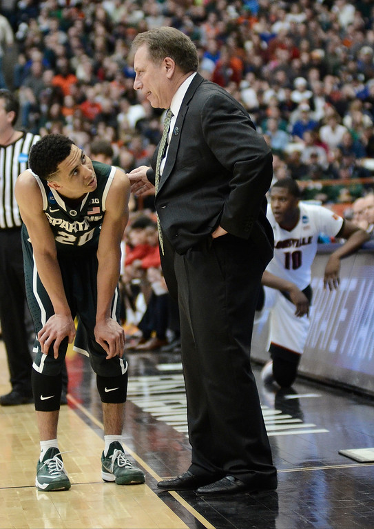 . Michigan State\'s Travis Trice (20) talks to head coach Tom Izzo during the second half of a regional final against Louisville in the NCAA men\'s college basketball tournament Sunday, March 29, 2015, in Syracuse, N.Y.  (AP Photo/Heather Ainsworth)