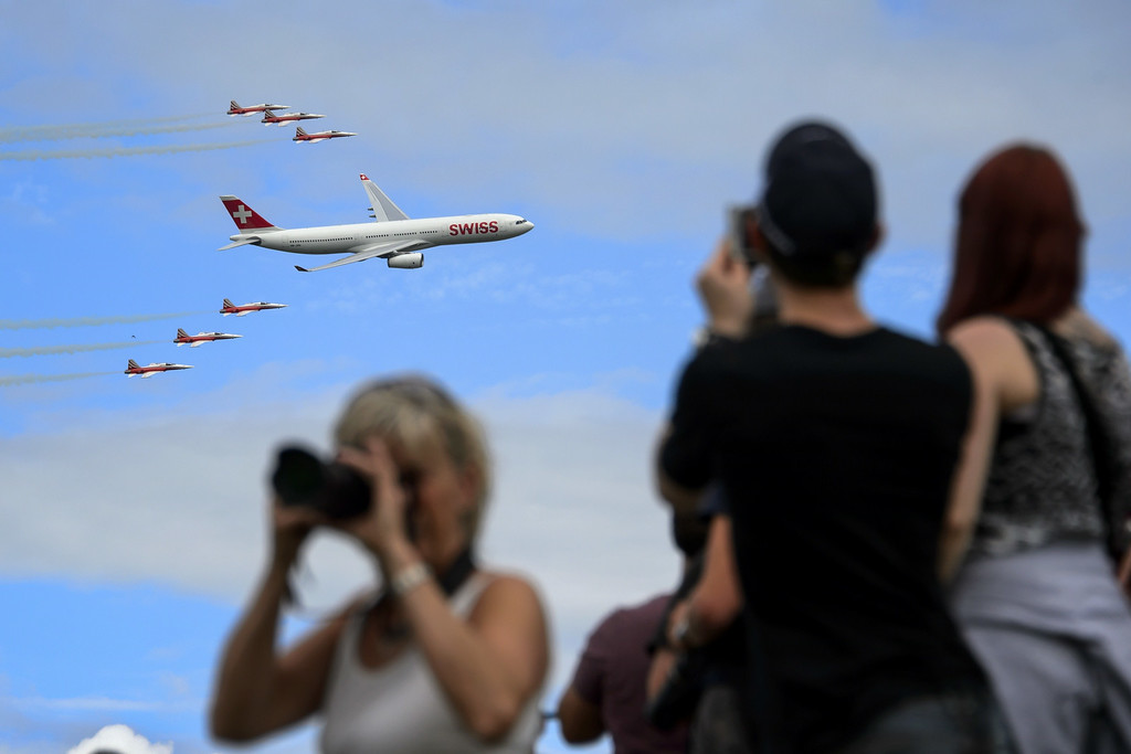 ". An Airbus A330 commercial plane of Swiss International Air Lines flies with fighter jets of the ""Patrouille Suisse\"" (Swiss patrol) on August 30, 2014 during the first day of AIR14 air show in Payerne, western Switzerland.  AFP PHOTO / FABRICE COFFRINI/AFP/Getty Images"