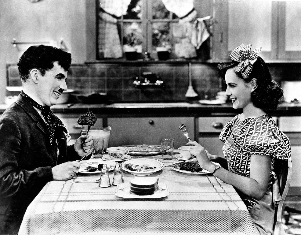 ". Actor, director and composer Charlie Chaplin and co-star Paulette Godard are shown eating a meal in a scene from Chaplin\'s 1936 movie ""Modern Times.\""  (AP Photo)"