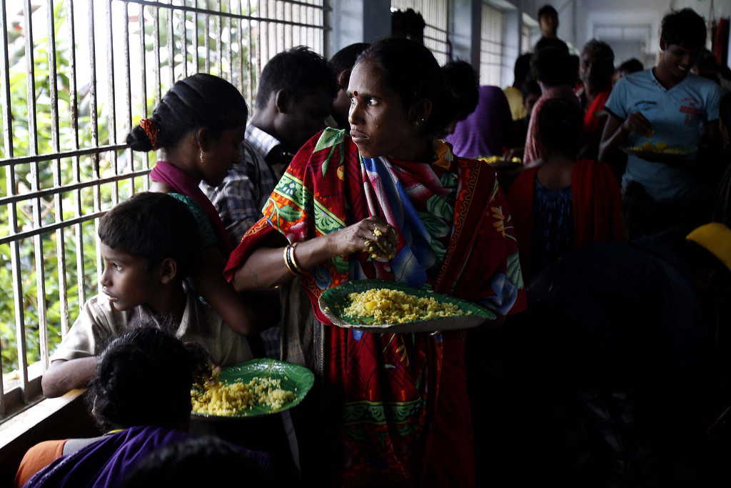 . Evacuated Indian villagers watch strong winds and rain as they eat food in a temporary cyclone shelter in  Chatrapur , in Ganjam district about 200 kilometers  (125 miles) from the eastern Indian city Bhubaneswar, India, Saturday, Oct. 12, 2013. Strong winds and heavy rains pounded India\'s eastern coastline Saturday, as hundreds of thousands of people took shelter from a massive, powerful Cyclone Phailin expected to reach land in a few hours. (AP Photo/Biswaranjan Rout)
