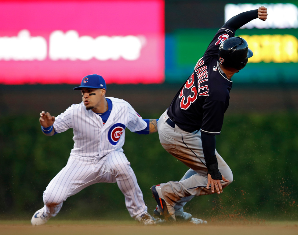 . Cleveland Indians\' Michael Brantley, right, is tagged out trying to steal second base by Chicago Cubs\' Javier Baez during the first inning of a baseball game Wednesday, May 23, 2018, in Chicago. (AP Photo/Jim Young)