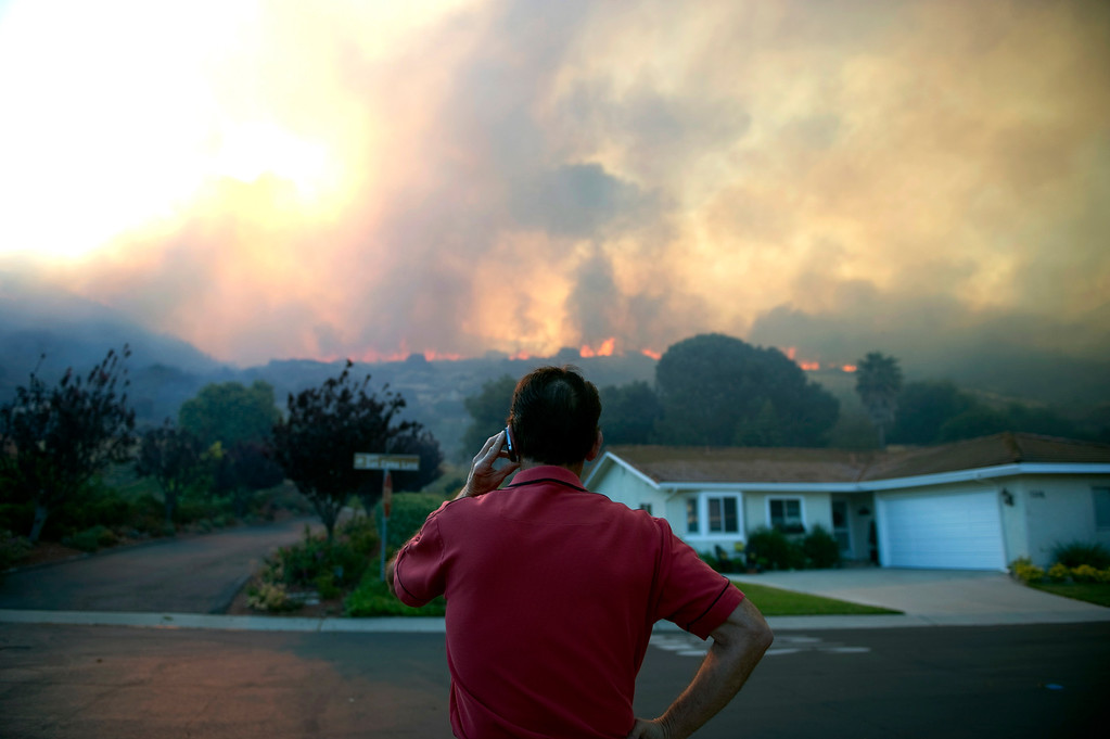 . Reuben Ruiz makes a phone call as he watches the flames from a brush fire in Camarillo, Calif., Thursday, May 2, 2013.  (AP Photo/The Ventura County Star, Troy Harvey)