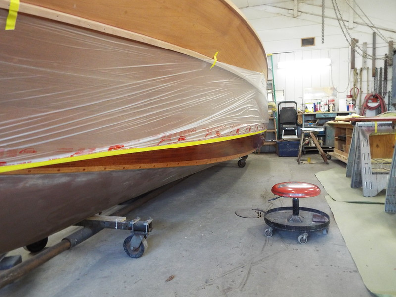 Port side masked at the water line with the first of three coats of epoxy applied down to the chine.