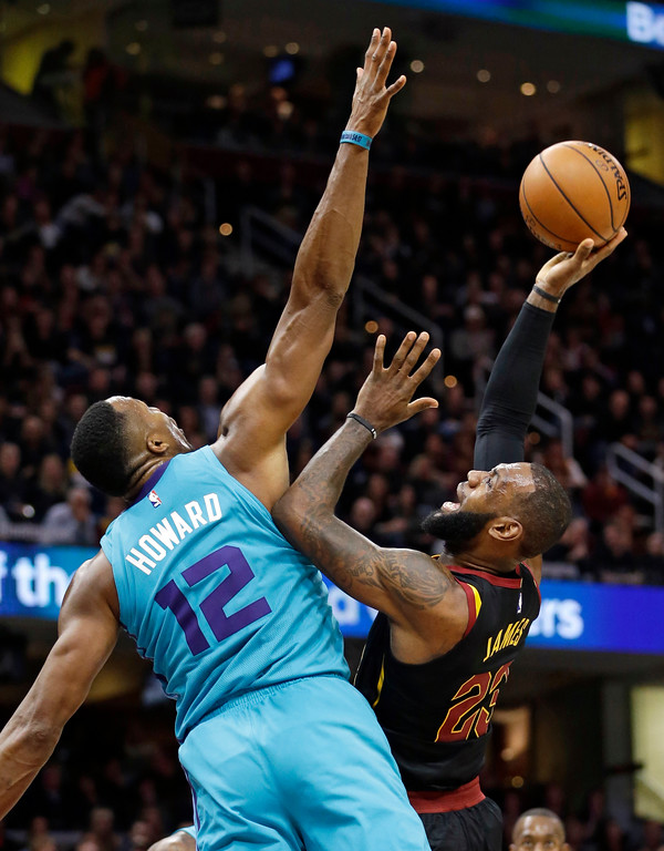 . Cleveland Cavaliers\' LeBron James, right, shoots over Charlotte Hornets\' Dwight Howard in the first half of an NBA basketball game, Friday, Nov. 24, 2017, in Cleveland. (AP Photo/Tony Dejak)