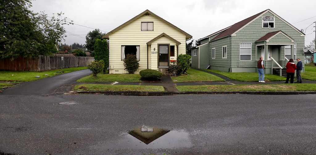 . This Monday, Sept. 23, 2013 photo shows the childhood home of Kurt Cobain, the late frontman of Nirvana, left, along an alley in Aberdeen, Wash. (AP Photo/Elaine Thompson)