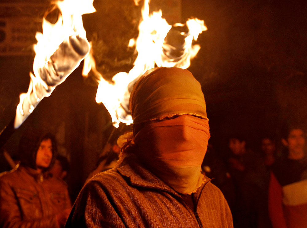 Description of . A masked activist of Jammu and Kashmir Liberation Front (JKLF) holds a torch as he participates in a protest march to mark International Human Rights Day in Srinagar, India, Monday, Dec. 10, 2012. More than 68,000 people, mostly civilians, have been killed since the outbreak of the insurgency in the region in 1989. Pakistan, Kashmiri separatist leaders and human rights groups have been demanding a reduction in India's military presence in Kashmir. (AP Photo/Mukhtar Khan)