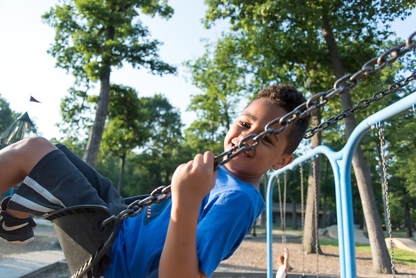 07/02/18 Wesley Bunnell | Staff Caleb Roman, age 10, plays on the swing set at Rockwell Park on Monday evening.