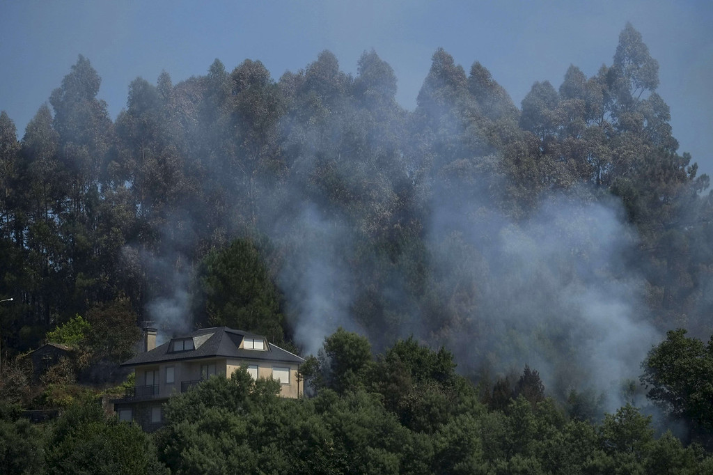 . Trees smoulder near a house at the site of a wildfire in O Rosal near Pontevedra, on August 29, 2013.  Spain is prone to forest fires in summer because of soaring temperatures, strong winds and dry vegetation.  Last year wildfires destroyed some 150,000 hectares of land in Spain from January to July, after one of the driest winters on record.  PEDRO ARMESTRE/AFP/Getty Images