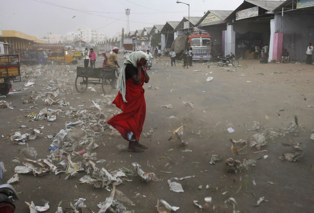 . An Indian woman tries to shield herself from the wind in Hyderabad, India, Tuesday, April 2, 2013. (AP Photo/Mahesh Kumar A.)