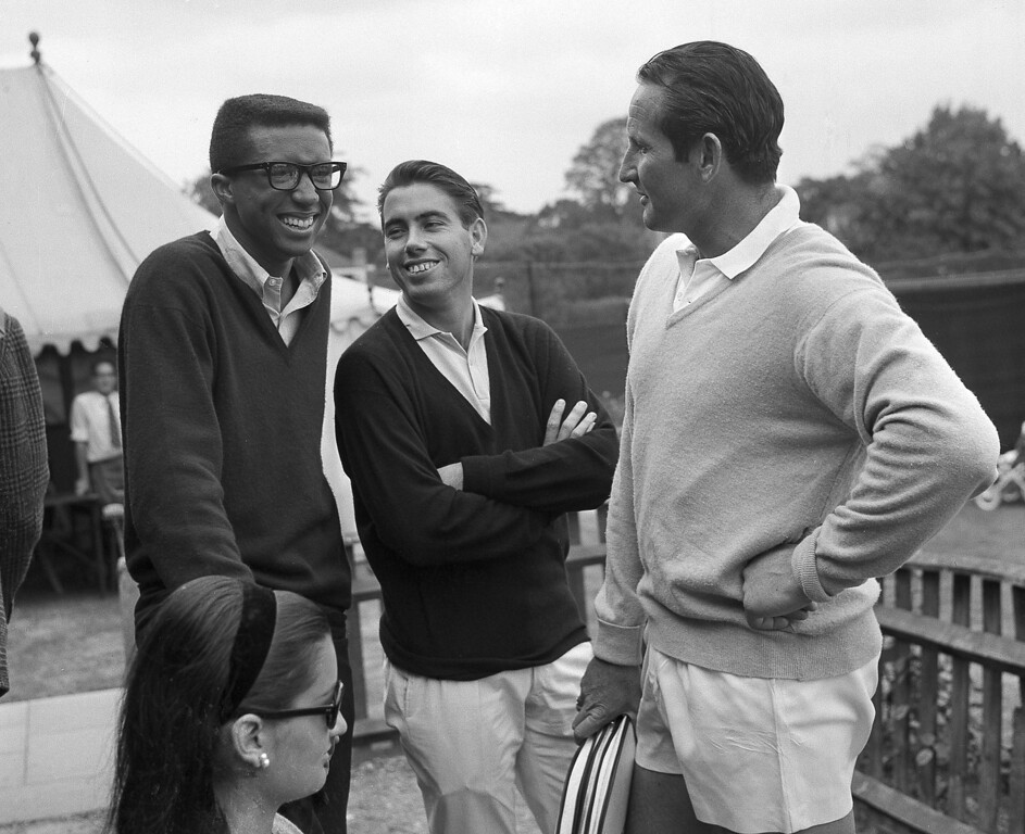 . Tennis star Arthur Ashe of the U.S., left, Manuel Santana of Spain, center, and Abe Segal of South Africa chat while waiting to go on court for the Kent Lawn Tennis championships at the Beckenham Club, near London, June 6, 1966. Ashe returns home immediately after the tournament as he is to be drafted to Vietnam for military service and will miss this year\'s Wimbledon championships.   (AP Photo/Bob Dear)