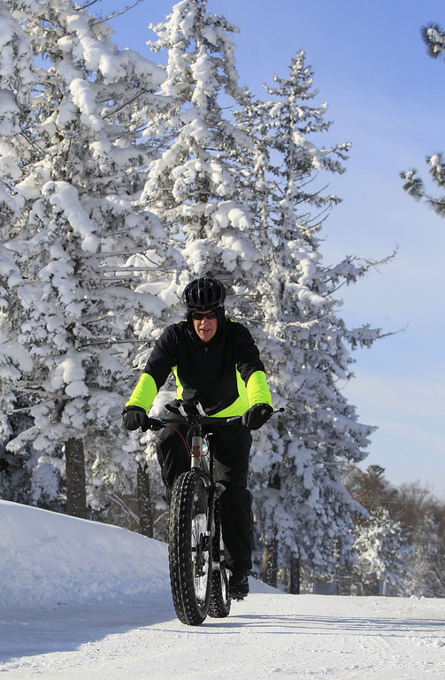 . Bill Graves rides his bike on the snow in Orchard Park,NY on Wednesday, Nov. 19, 2014.  A ferocious lake-effect storm left the Buffalo area buried under 6 feet of snow Wednesday, trapping people on highways and in homes, and another storm expected to drop 2 to 3 feet more was on its way. (AP Photo/The Buffalo News, Harry Scull Jr.)