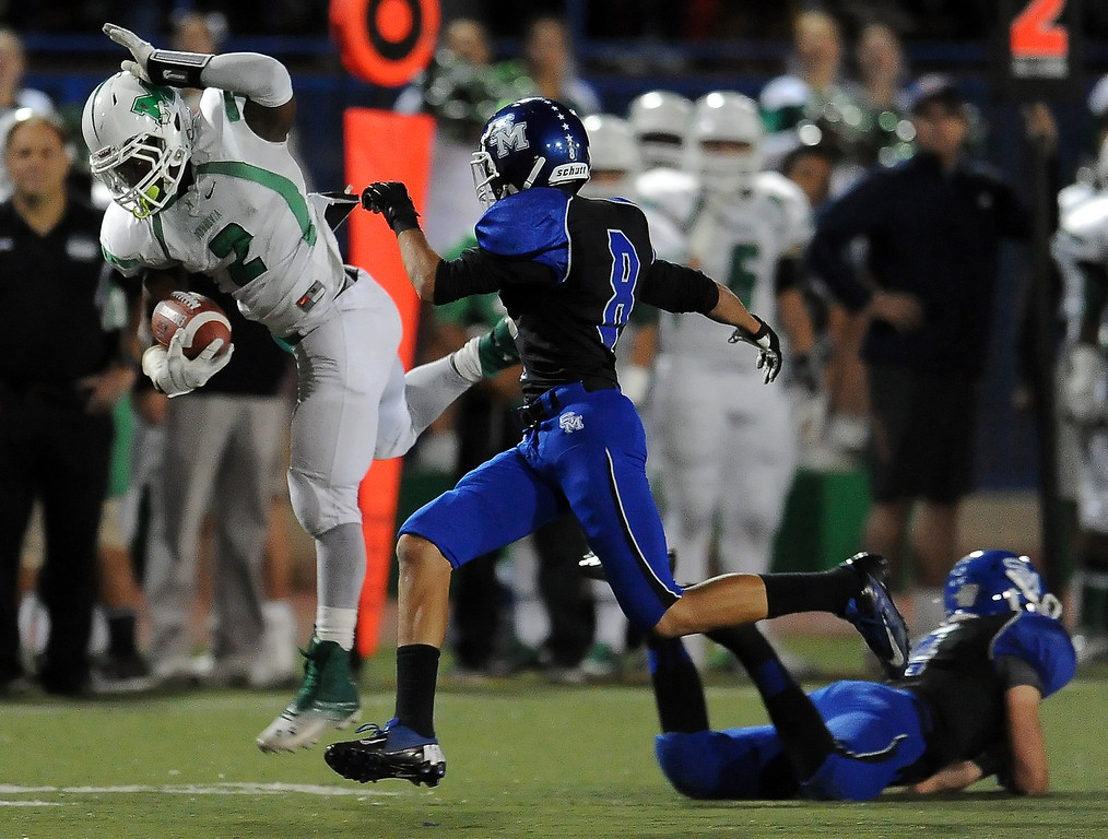 . Monrovia\'s Kurt Scoby (2) leaps over San Marino\'s Mark Wicke (4) for a first down in the first half of a prep football game at Monrovia High School in Monrovia, Calif., on Friday, Nov. 8, 2013.    (Keith Birmingham Pasadena Star-News)