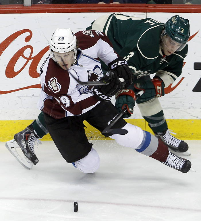 . Colorado Avalanche center Nathan MacKinnon (29) and Minnesota Wild center Charlie Coyle, right, tangle as they chase the puck during the first period of an NHL hockey game in St. Paul, Minn., Friday, Nov. 29, 2013. (AP Photo/Ann Heisenfelt)