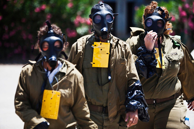 . Israeli soldiers, wearing gas masks, take part in a drill simulating a chemical attack in Azur, near Tel Aviv May 28, 2013. Israel continued on Tuesday with its annual home front defense exercise, launched on Monday, preparing soldiers and civilians for missile attacks. REUTERS/Nir Elias