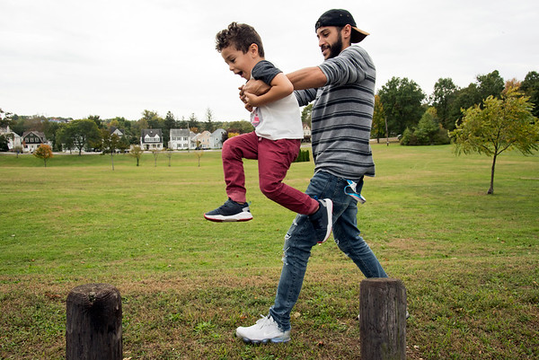 10/07/19 Wesley Bunnell | StaffrrYoussef Benayad helps his three year old son Zachariah jump from log to log at Walnut Hill Park on Monday afternoon as the two played.