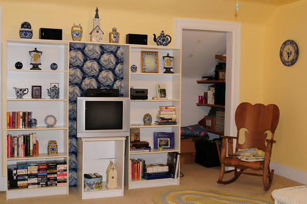 Front room  left side. A sink; mirror and toilet are under the eaves just to the left of this photo. A small refrigerator and microwave are in the closet on right. Rocking chair is no longer there.