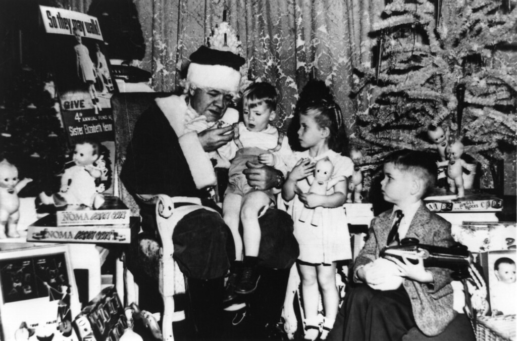 . 17 DEC 1947:  BABE RUTH IS DRESSED AS SANTA CLAUS WITH THREE YEAR-OLD JIMMY MCCALL ON HIS KNEE AND JANE GREENFIELD AT HIS SIDE DURING A CHRISTMAS PARTY FOR 65 YOUNG POLIOMYELITIS VICTIMS GIVEN BY THE SISTER ELIZABETH KENNY FOUNDATION IN THE HOTEL ASTOR IN NEW YORK CITY. (Photo by  Allsport/Getty Images)