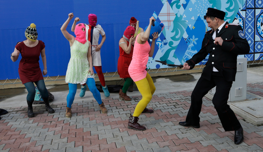 . A Cossack militiaman attacks Nadezhda Tolokonnikova as she and fellow members of the punk group Pussy Riot, including Maria Alekhina, center, in the pink balaclava, stage a protest performance in Sochi, Russia, on Wednesday, Feb. 19, 2014. The group had gathered in a downtown Sochi restaurant, about 30km (21miles) from where the Winter Olympics are being held. They ran out of the restaurant wearing brightly colored clothes and ski masks and were set upon by about a dozen Cossacks, who are used by police authorities in Russia to patrol the streets. (AP Photo/Morry Gash)