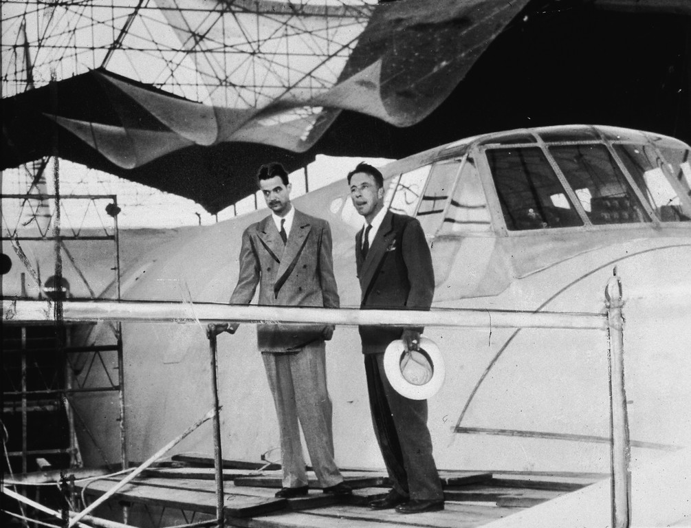 . American industrialist, aviator, and film producer Howard Hughes (1905 - 1976) (left) and an unidentified man stand on a platform outside the cockpit of the Spruce Goose, a massive sea plane designed and built (out of wood) by Hughes, Los Angeles, CA, 1947. This photograph has been retouched. (Photo by Hulton Archive/Getty Images)