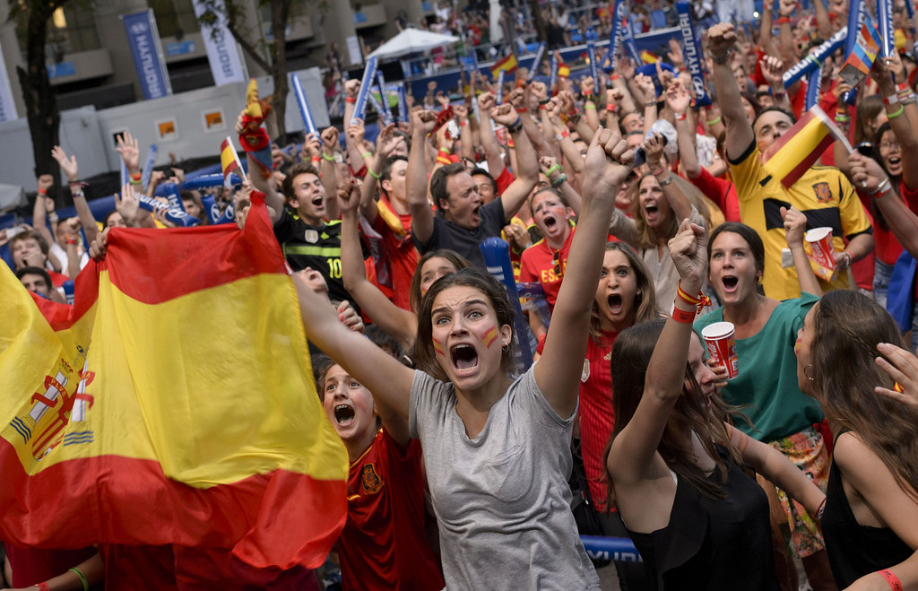 . Spain\'s supporters celebrate their team\'s first goal as they watch the 2014 FIFA World Cup football match between Spain and Netherlands on a giant screen near the Santiago Bernabeu stadium in Madrid on June 13, 2014.  AFP PHOTO / DANI POZO/AFP/Getty Images
