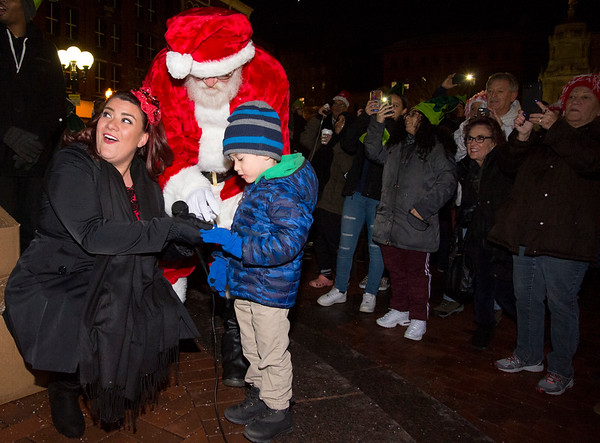 12/05/19 Wesley Bunnell | StaffrrThe New Britain Christmas tree was lit on Thursday night in Central Park complete with a visit from Santa Clause who rode in on a NBFD fire truck. Mayor Erin Stewart and Santa look on as three year old James Ciccarillo helps to light the tree.