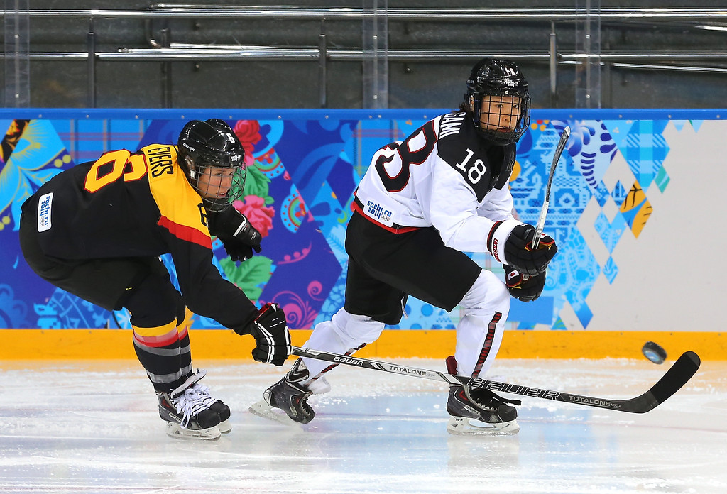 . Tomoko Sakagami #18 of Japan passes the puck against Bettina Evers #6 of Germany in the third period during the women\'s Ice Hockey Preliminary Round Group B game on day six of the Sochi 2014 Winter Olympics at Shayba Arena on February 13, 2014 in Sochi, Russia.  (Photo by Martin Rose/Getty Images)