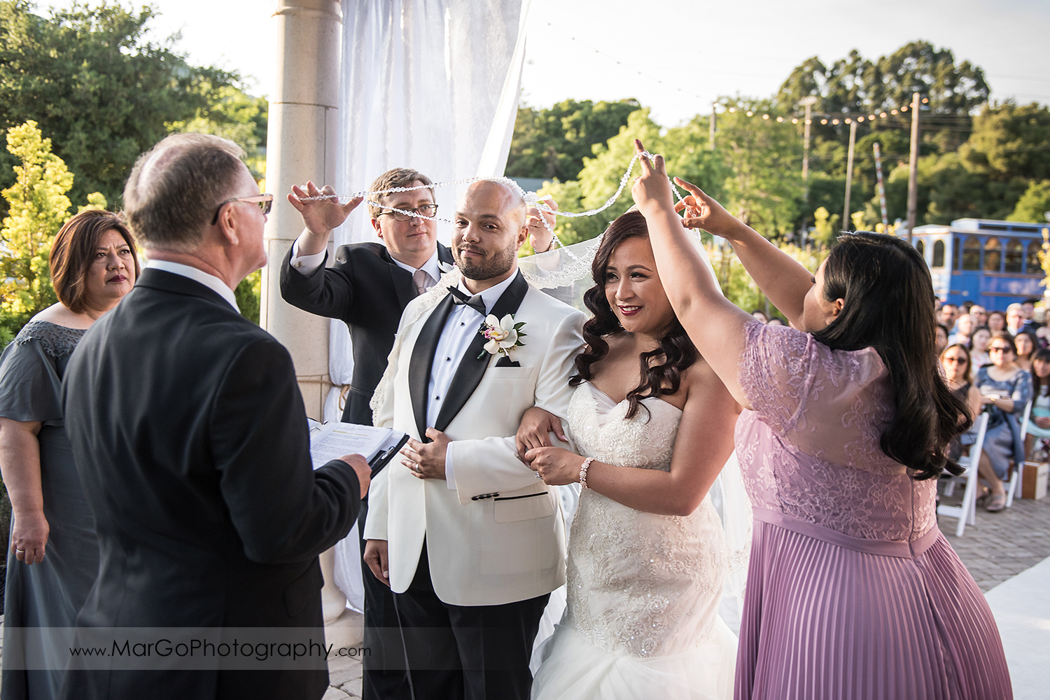 sponsors placing lasso rosary around bride and groom during wedding ceremony at Sunol's Casa Bella