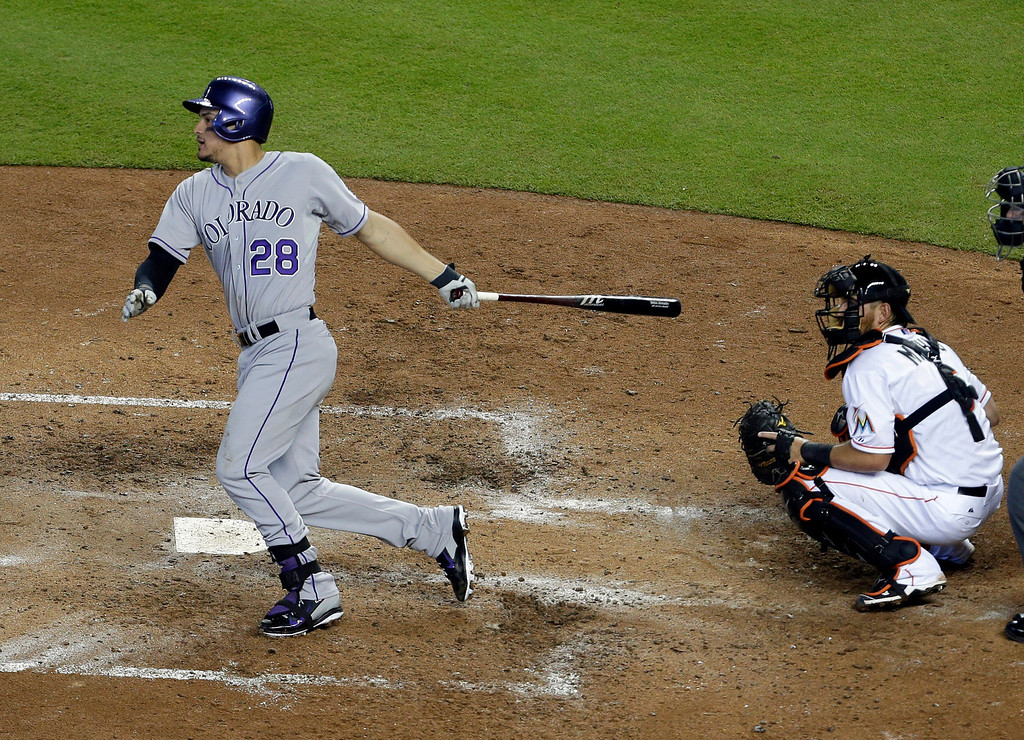. Colorado Rockies\' Nolan Arenado follows through with an RBI-single to score Troy Tulowitzki as Miami Marlins catcher Jeff Mathis looks on during the fifth inning of a baseball game, Thursday, April 3, 2014, in Miami. (AP Photo/Lynne Sladky)