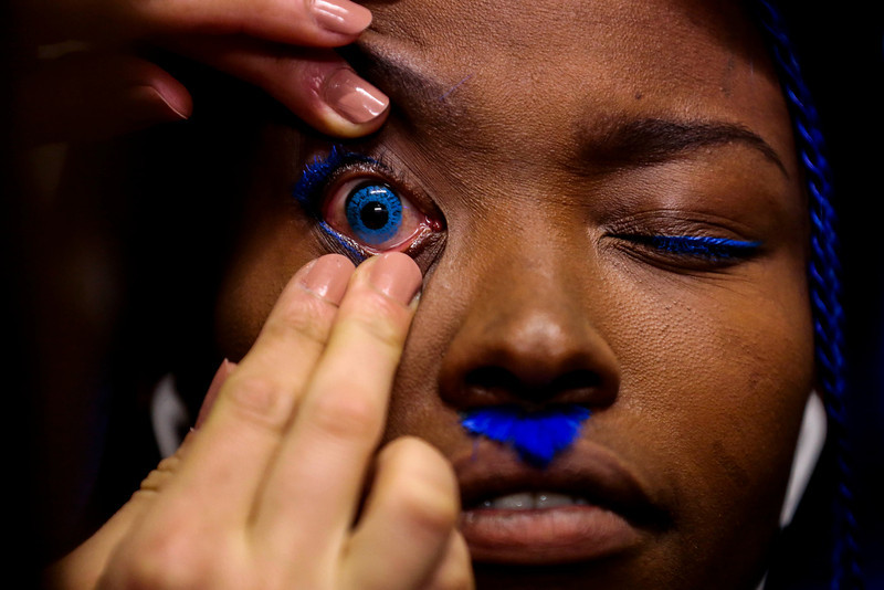. A model gets prepared with a blue contact lens to present a creation of Patrick Mohr\'s Autumn Winter 2014 collection during the Mercedes Benz Fashion Week in Berlin, Tuesday, Jan. 14, 2014. (AP Photo/Markus Schreiber)