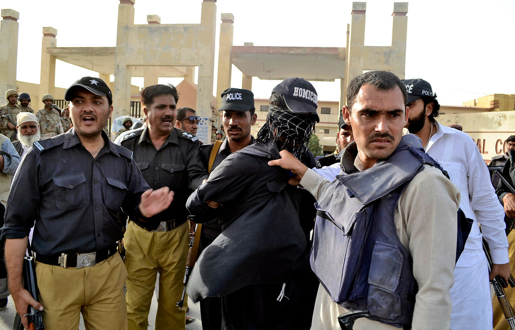 . Pakistani police officers detain an alleged militant from the site of a gun battle at a hospital, in Quetta, Pakistan, Saturday, June 15, 2013.  (AP Photo/Arshad Butt)